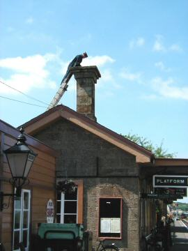 2005 - A member of the station staff fixing anti-bird netting atop the Bristol and Exeter Railway chimney on Williton station in June. This work is licenced under a Creative Commons Licence. © Jon Tooke