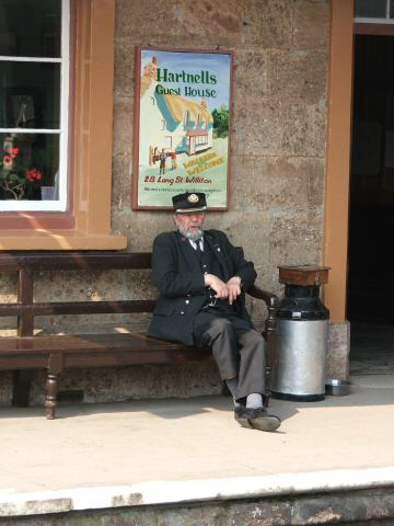 2006 - Williton Stationmaster Chris van den Arend relaxes between arrivals on 11 May. This work is licenced under a Creative Commons Licence. © Fotophile69