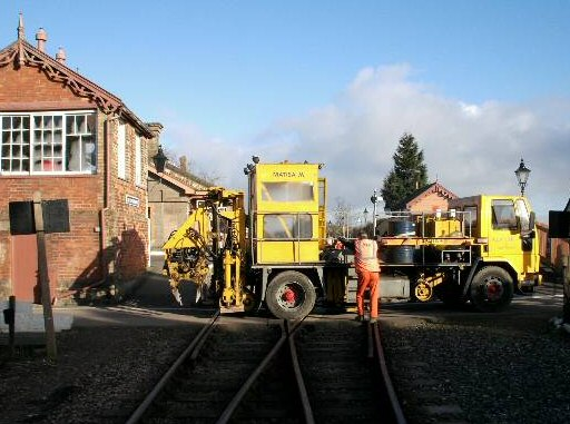 2007 - Brought in to tamp the relays at Watchet and Castle Hill, here is the road-rail vehicle at Williton Level Crossing on 13 March. This work is licenced under a Creative Commons Licence. © Pat Langan
