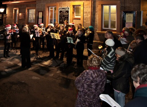 2010 - Having arrived by steam train, the massed carollers at Williton Station on the evening of 14 December. This work is licenced under a Creative Commons Licence. © Mike Dunse