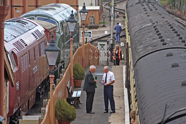 2011 - A busy scene at Williton Station - a discussion between staff on the platform whilst TTI Jacqui Lakin returns to the platform after the long walk taking refreshments from the buffet carriage to the footplate crew - seen on 28 August. This work is licenced under a Creative Commons Licence. ©Martin Hope