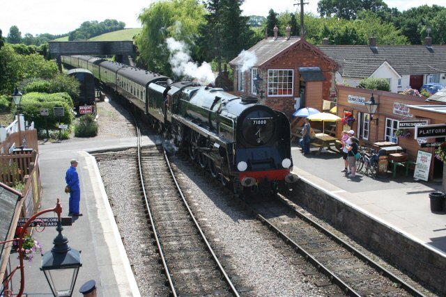 2011 - Viewed from the new footbridge BR 4-6-2 No. 71000 Duke of Gloucester arrives at Williton with a Minehead-bound train on 23 July. This work is licenced under a Creative Commons Licence. © Peter Nicholson