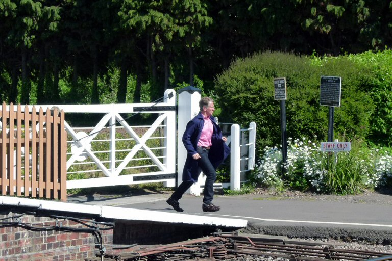 "2012 Michael Portillo sprints to close the crossing gates at Williton during the filming of one of his ""Great British Railway Journeys"" on 23 May. This work is licenced under a Creative Commons Licence. © Bev Zehetmeier"