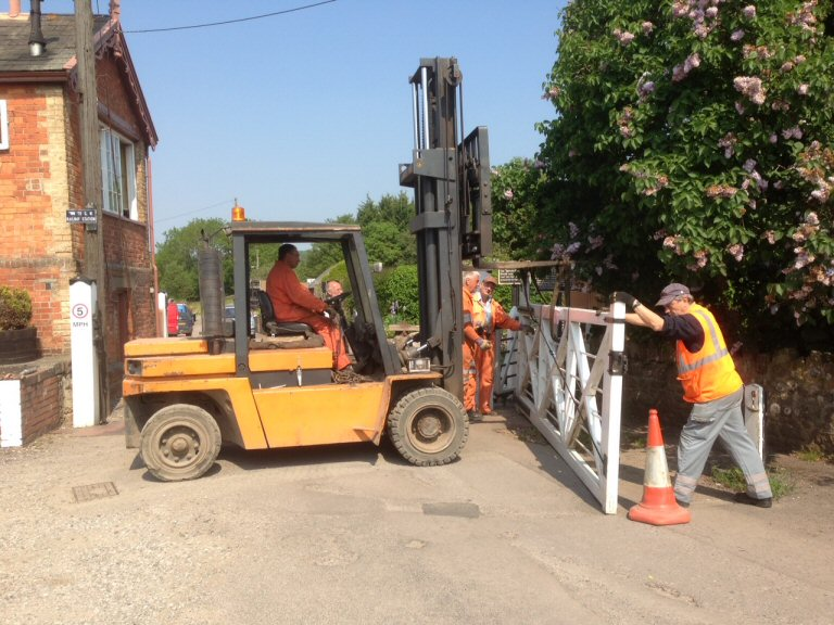 2013 - Williton Crossing downside gate being lifted to insert spacers in the hinges to correct droop on 6 June. This work is licenced under a Creative Commons Licence. © Robin White.