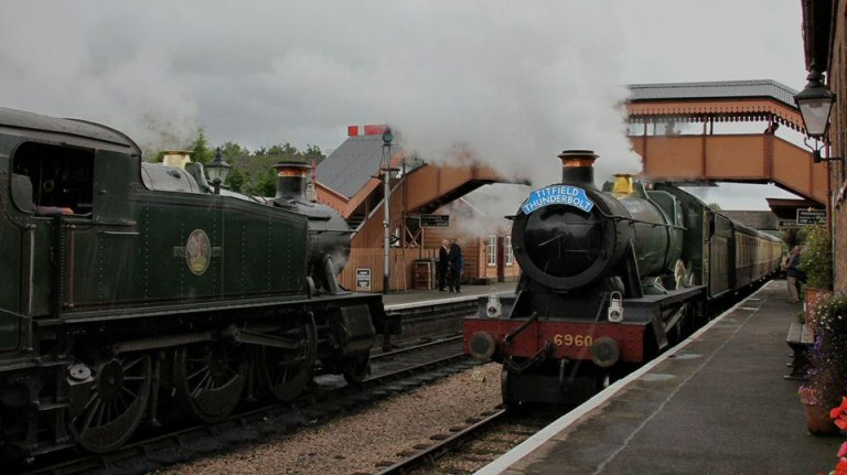 2015 - Complete with 'Titfield Thunderbolt' headboard GWR 4-6-0 No. 6960 'Raveningham Hall' arrives at Williton in heavy rain on 14 September. This work is licenced under a Creative Commons Licence. © Bev Zehetmeier.