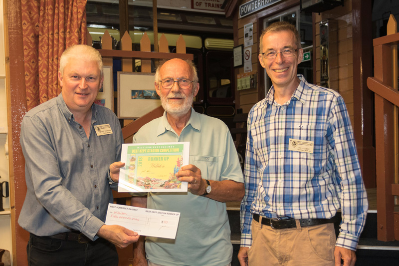 2018.07.27 Paul Conibeare, WSR General Manager, presents Williton Station Master John Parsons with the 2018 runner up certificate in the Best Kept Station Competition, organised by WSR Chairman Ian Coleby (right). © Jacquie Green.