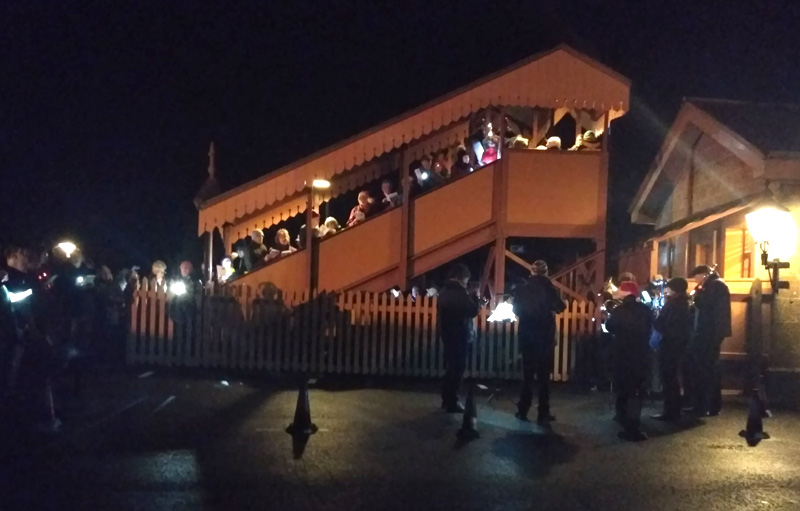 2018.12.11 Carol Train passengers from Bishops Lydeard line platform and bridge as the band plays from the car park. © Chris Hooper.