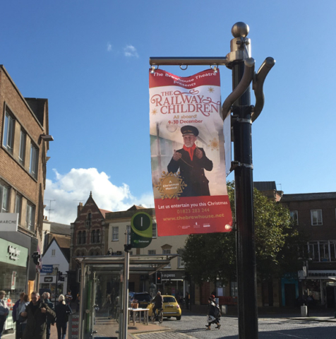 2019.10.17 Williton station master seen hanging around six posts in the centre of Taunton. Promoting The Brewhouse Theatre production of The Railway Children (and the WSR!) © John Parsons