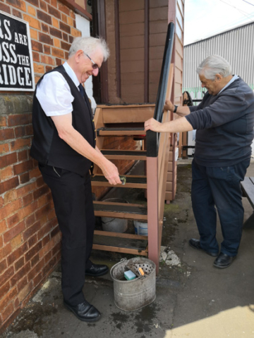 2019.07.10. Signal steps up-scrubbing . Signalman Simon Prisk makes the stairs to his box sparkle again on Williton Station platform. Philip Dale (R) admires the work. © Richard Salt