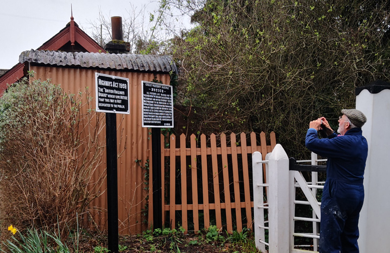 2019.03.21 Post repainting of the official notices by the Williton road crossing, Station Master John Parsons checks the spelling! © Richard Salt